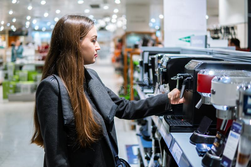 Cliente fêmea moderno esperto que escolhe a máquina do café foto de stock