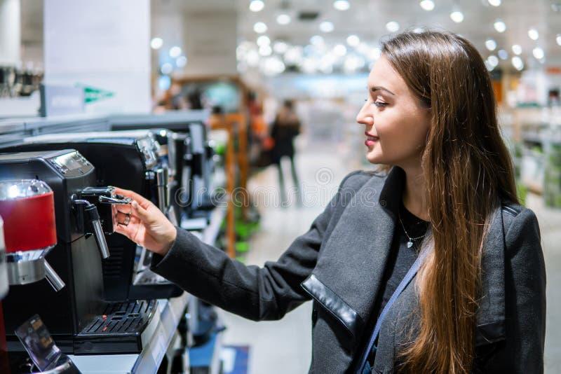 Cliente fêmea moderno esperto que escolhe a máquina do café fotos de stock royalty free