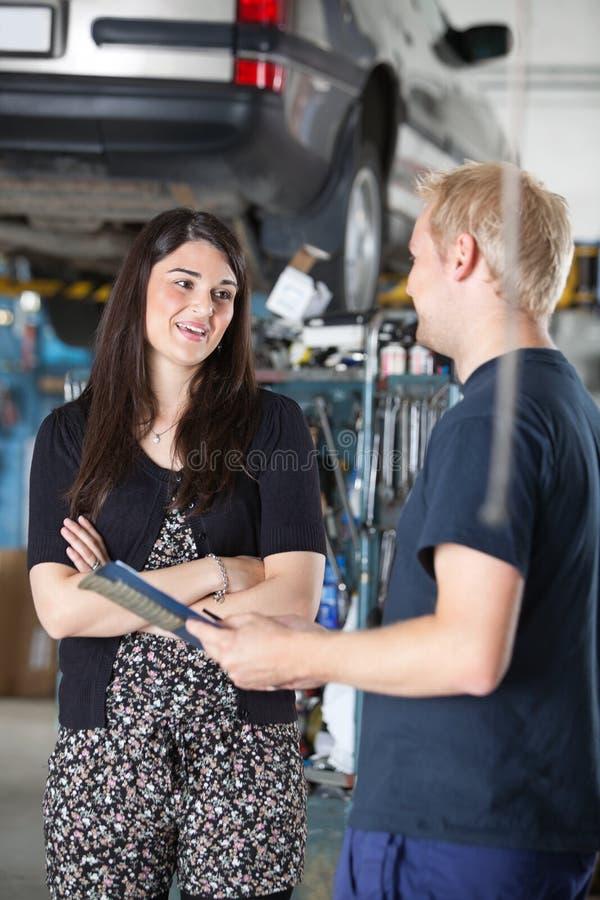 Cliente fêmea na loja do mecânico imagem de stock royalty free