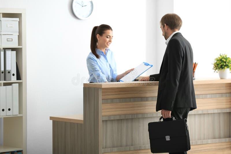 Cliente fêmea novo da reunião do recepcionista fotografia de stock