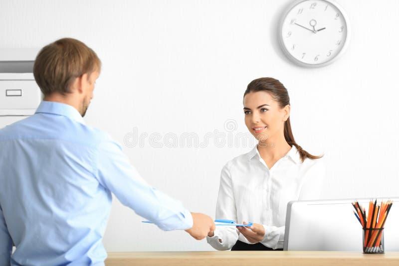 Cliente fêmea novo da reunião do recepcionista imagens de stock