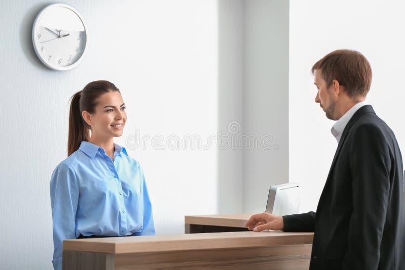 Cliente fêmea novo da reunião do recepcionista imagens de stock royalty free