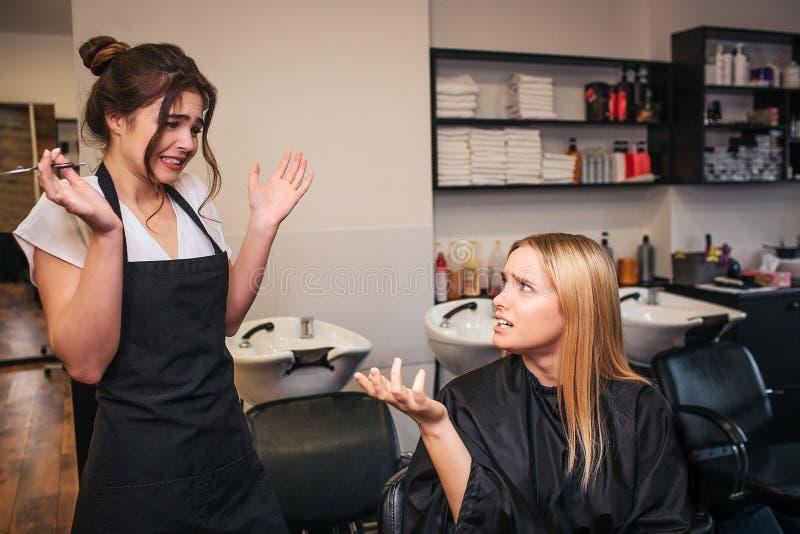 Cliente fêmea novo louro virado que responsabiliza o cabeleireiro como um mau feito corte de cabelo Luta no salão de beleza fotos de stock royalty free