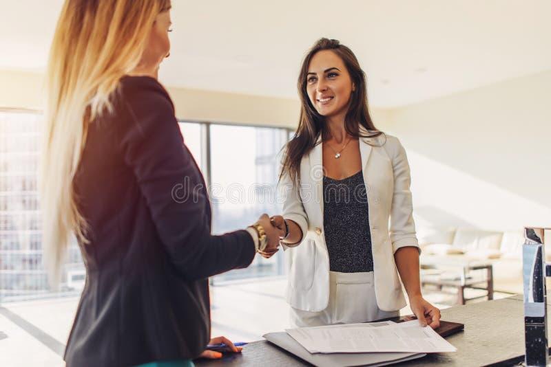 Cliente fêmea que agita as mãos com o mediador imobiliário que concorda assinar um contrato que está no apartamento de estúdio mo fotografia de stock