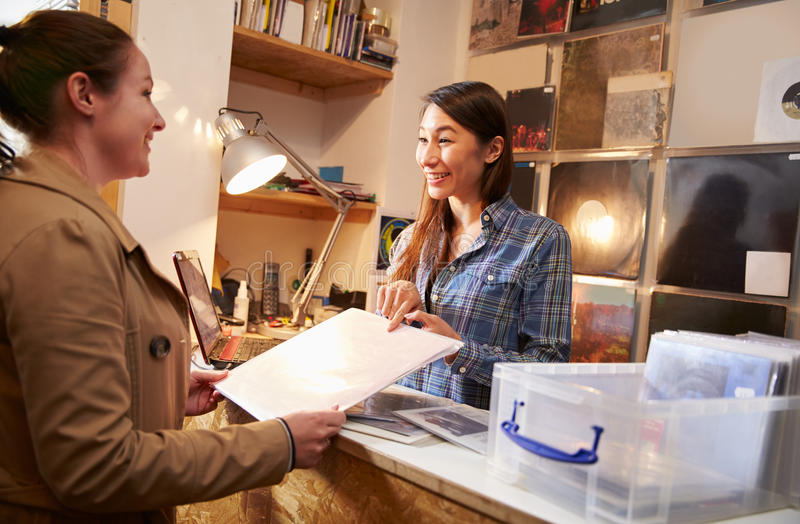 Cliente fêmea que está sendo servido no contador de uma loja do registro imagem de stock royalty free