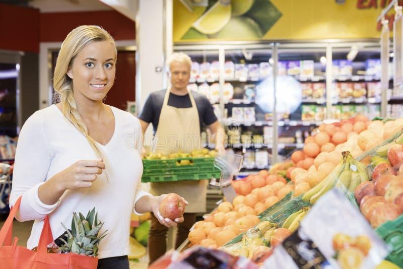 Cliente fêmea que guarda Apple no supermercado imagens de stock royalty free