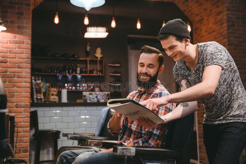 Cliente felice del contenuto e del barbiere che guarda attraverso la rivista fotografie stock libere da diritti