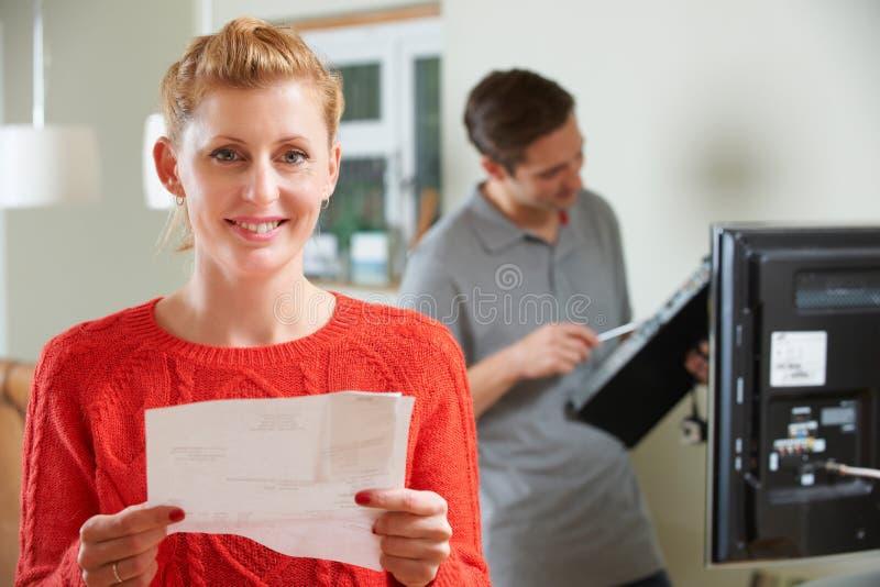 Cliente feliz com a instalação da tevê de Bill For imagem de stock