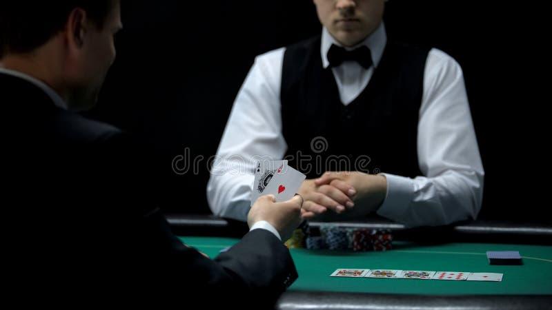 Cliente feliz do casino que olha a boa combinação dos cartões no pôquer, mão forte foto de stock