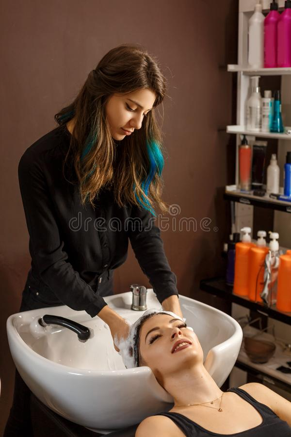 Cliente feliz en un salón de pelo que se lava el pelo con champú imagen de archivo