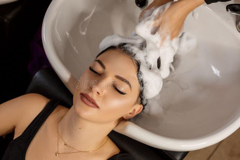 Cliente feliz en un salón de pelo que se lava el pelo con champú fotografía de archivo libre de regalías