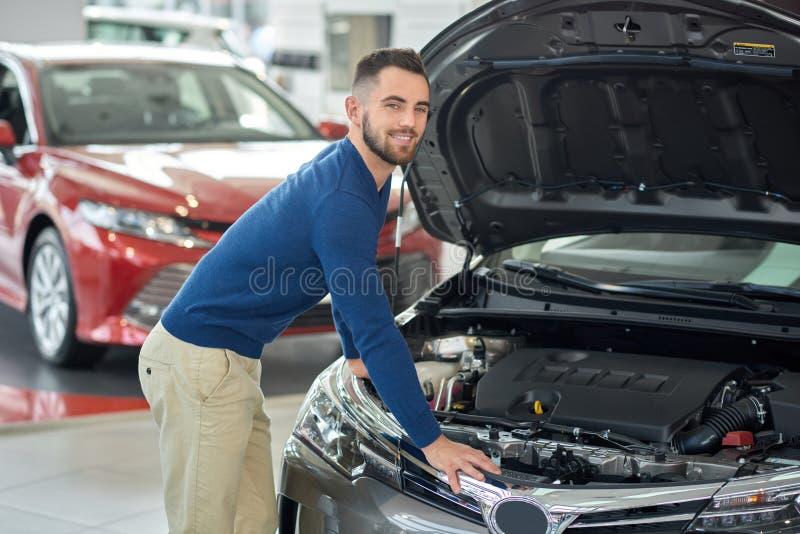 Cliente feliz que comprueba el auto en salón del coche antes de comprarlo fotos de archivo