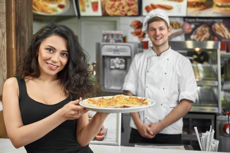 Cliente feliz que mantém a pizza nas mãos e que levanta no café foto de stock royalty free