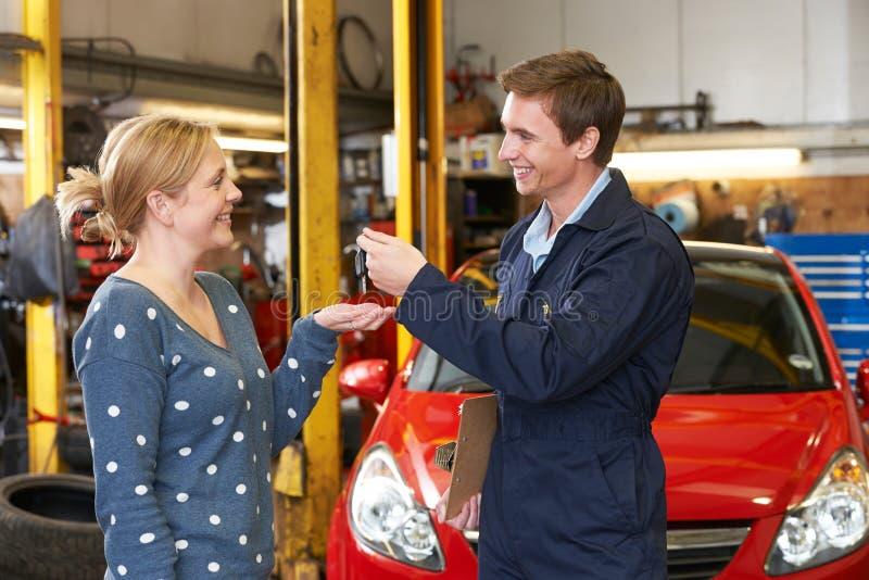 Cliente feliz que recolhe o carro da garagem foto de stock royalty free