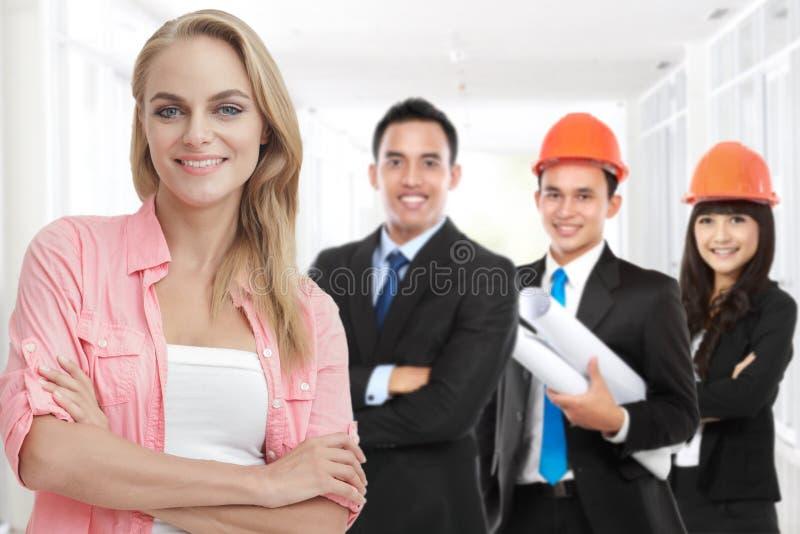 Cliente feliz que se coloca delante de su contratista o buil de la casa fotos de archivo
