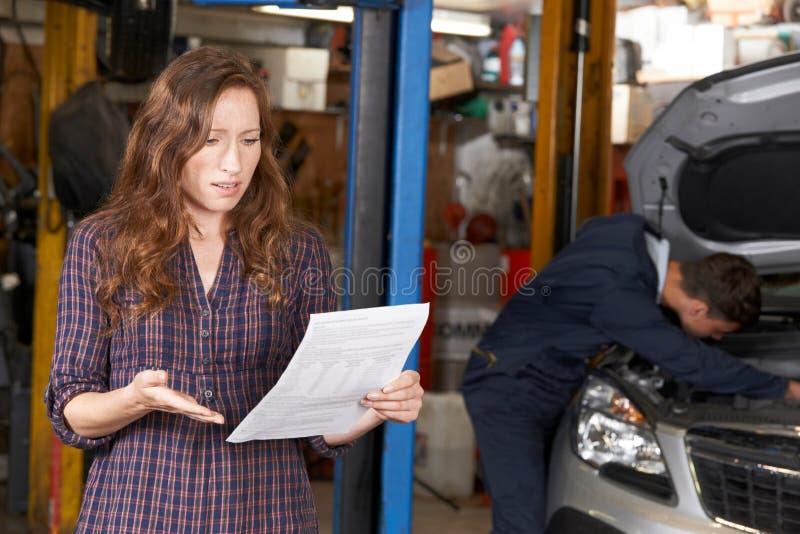 Cliente femenino chocado que mira el garaje Bill imagenes de archivo