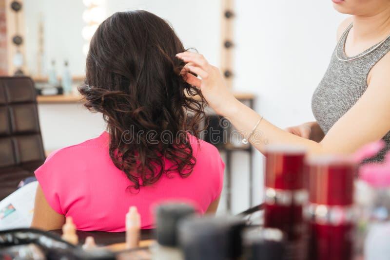 Cliente femenino con el pelo oscuro y el peluquero que hacen el peinado imágenes de archivo libres de regalías