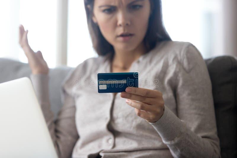 Cliente femenino confuso que sostiene la tarjeta de crédito enojada con el pago en línea imagen de archivo libre de regalías