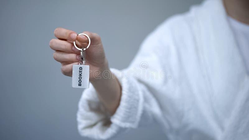 Cliente femenino en la albornoz que lleva a cabo llaves con la palabra reservada, hotel turístico de lujo fotos de archivo