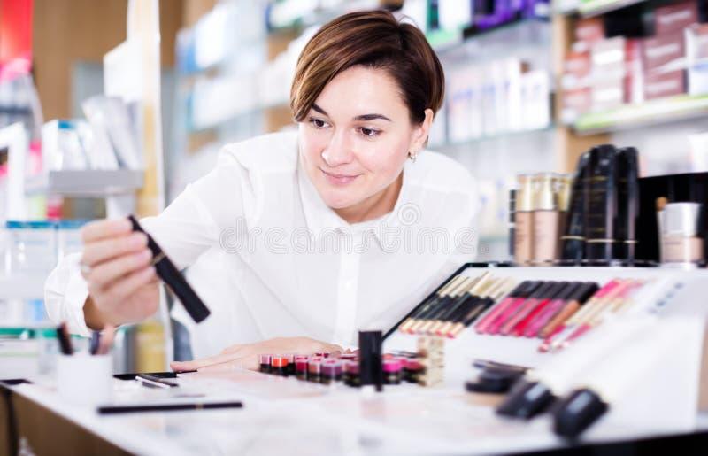 Cliente femenino joven que busca artículos del maquillaje fotografía de archivo