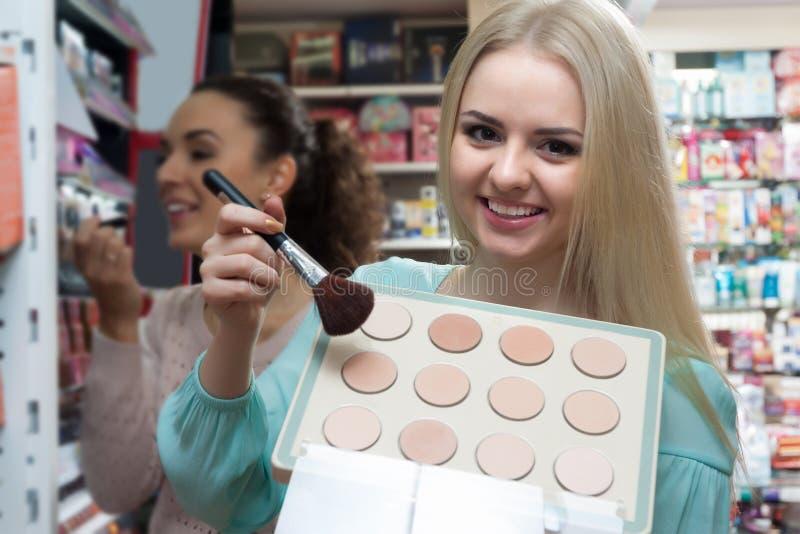 Cliente femenino que elige el polvo de la piel fotos de archivo