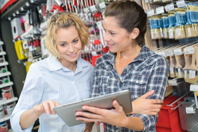 Cliente femenino que muestra la tableta digital al vendedor en ferretería imagenes de archivo