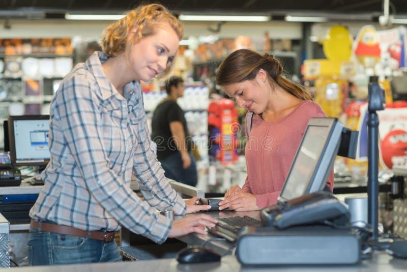 Cliente femenino que paga en el escritorio de efectivo con el terminal en supermercado foto de archivo libre de regalías