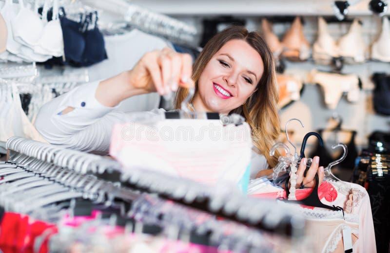 Cliente feminino escolhendo brassiere em loja de roupas íntimas fotos de stock