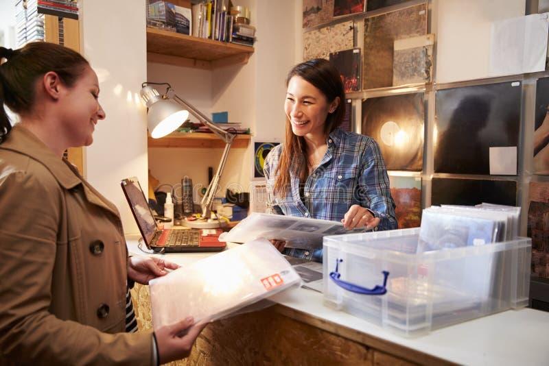 Cliente femminile che è servito al contatore di un negozio record immagine stock libera da diritti