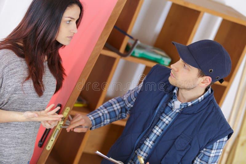 Cliente femminile che parla con fissatore della porta-serratura immagine stock