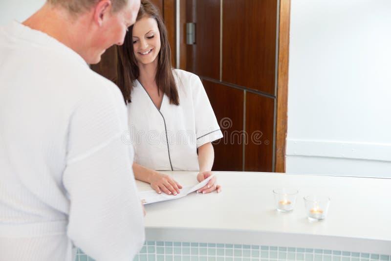 Cliente femminile del maschio e del receptionist alla stazione termale immagini stock libere da diritti