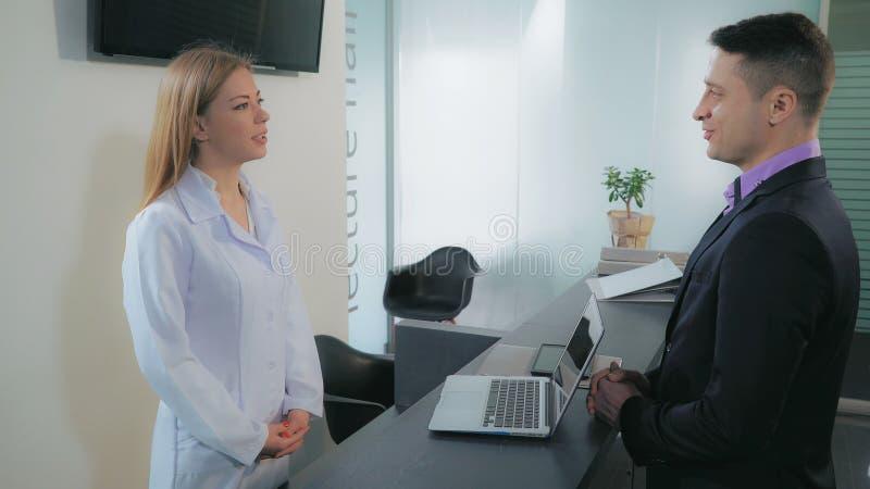 Cliente femminile di saluto in clinica dentaria fotografia stock