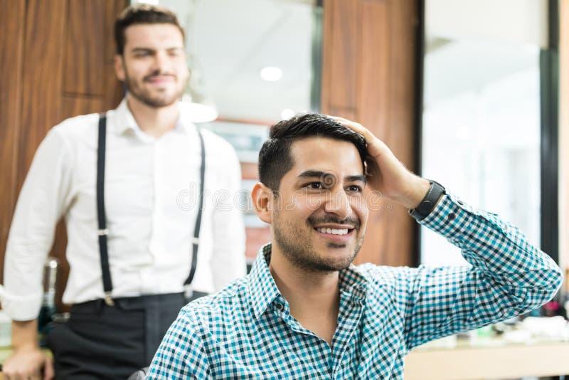 Cliente hermoso que examina el pelo recientemente cortado en Barber Shop foto de archivo