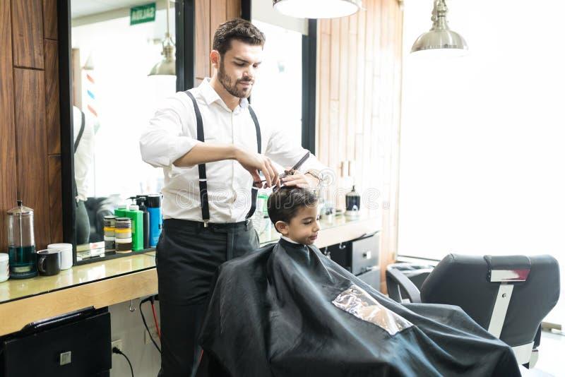 Cliente innocente di Cutting Hair Of del parrucchiere a Barber Shop immagini stock