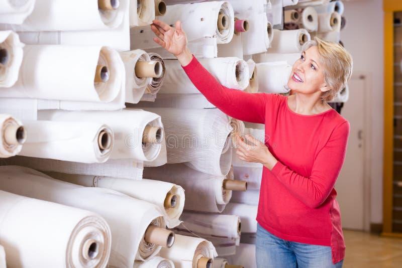 Cliente invecchiato allegro della donna che cerca bello tessuto nel tex fotografia stock
