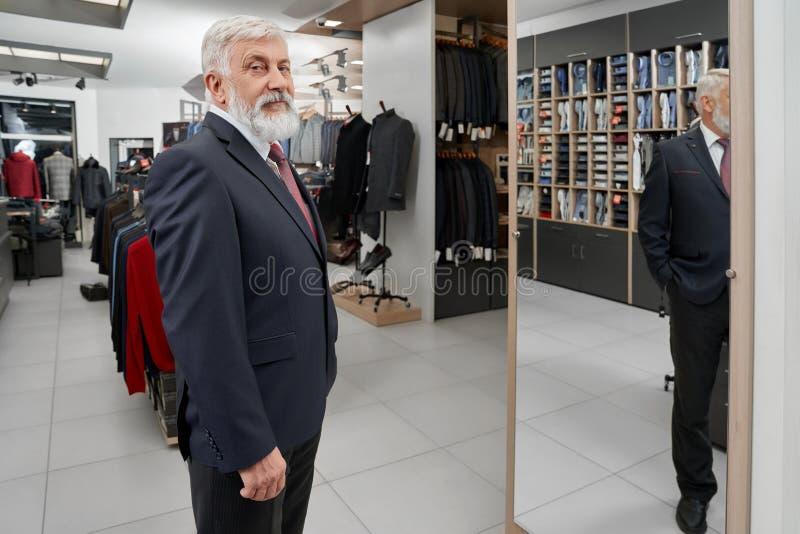 Cliente mais idoso que olha a câmera ao tentar no terno formal foto de stock royalty free