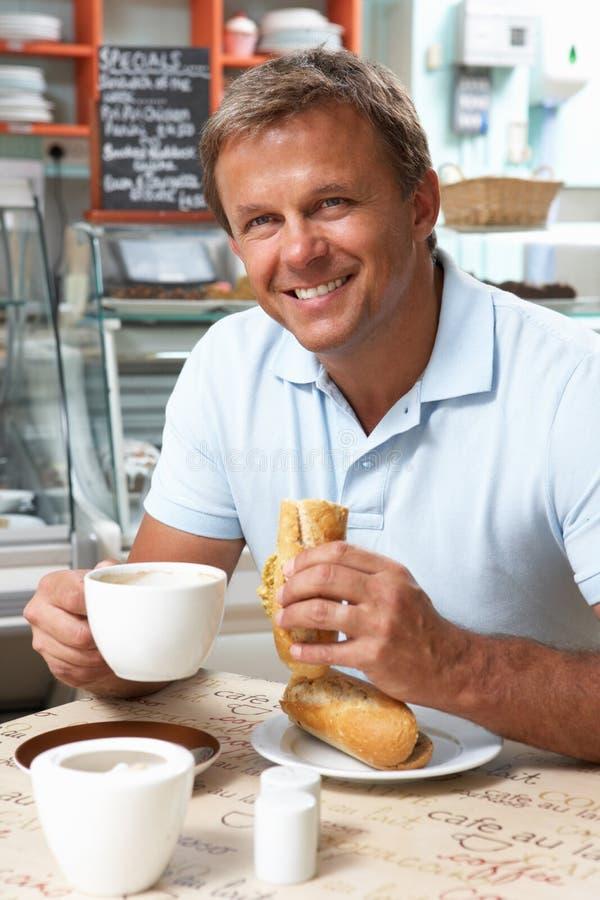Cliente maschio che gode del panino e del caffè in caffè fotografia stock libera da diritti