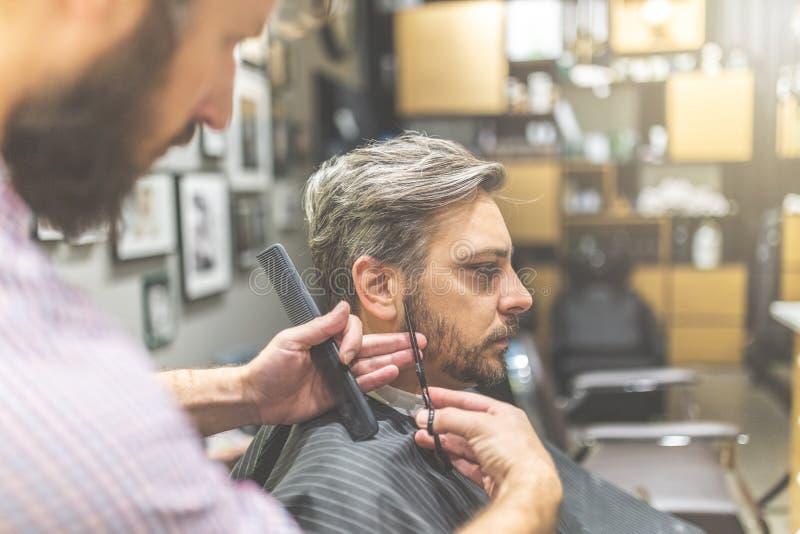 Cliente maschio che ottiene taglio di capelli dal parrucchiere fotografie stock