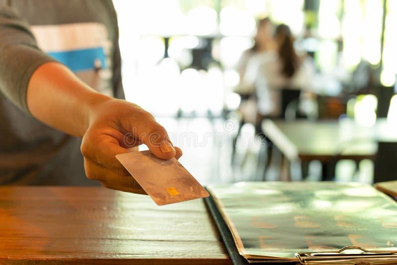Cliente maschio che paga attraverso la carta di credito alla caffetteria fotografia stock