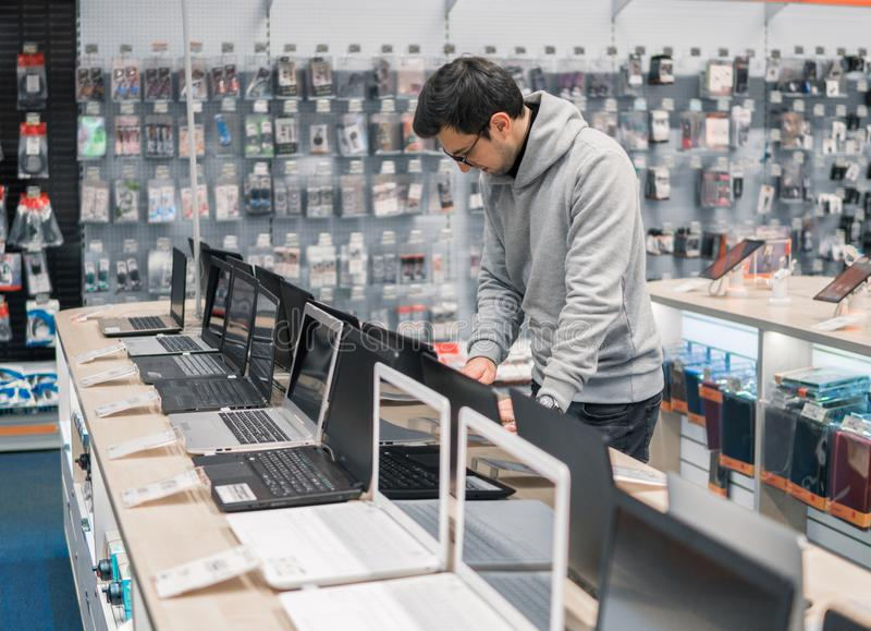 Cliente maschio moderno che sceglie computer portatile nel deposito di computer immagine stock