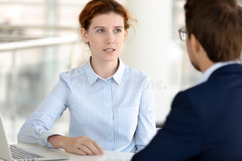 Cliente masculino asesor que habla del corredor de seguros de sexo femenino serio en el encuentro foto de archivo