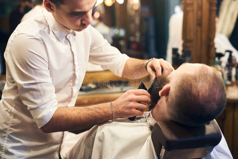Cliente masculino com a barba que senta-se na cadeira do cabeleireiro Homem s?rio com a barba marrom longa Estilo popular moderno fotografia de stock