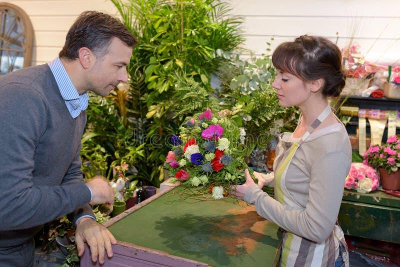 Cliente masculino de ajuda do vendedor para escolher flores fotografia de stock