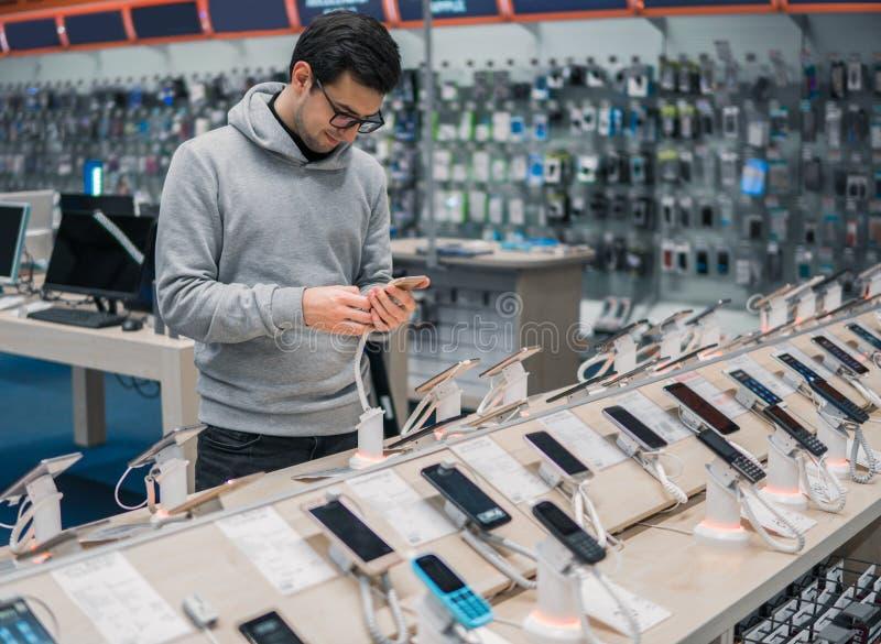 Cliente masculino elegante que elige smartphone imágenes de archivo libres de regalías