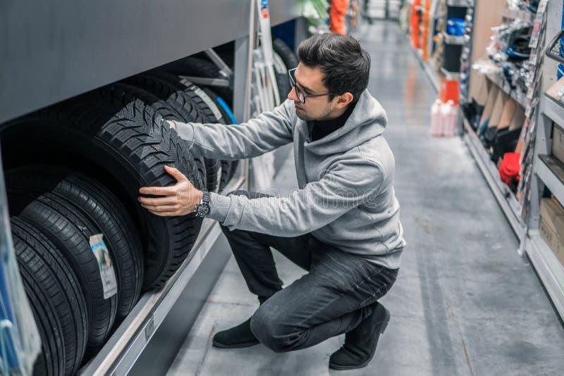 Cliente masculino esperto que escolhe pneus novos no supermercado imagem de stock