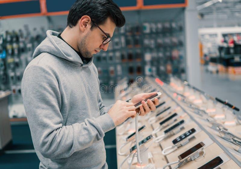 Cliente masculino feliz que escolhe o smartphone imagens de stock
