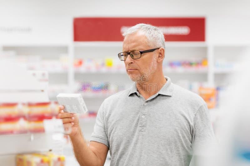 Cliente masculino mayor con la droga en la farmacia imagen de archivo libre de regalías