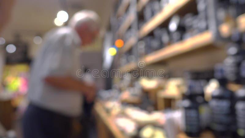 Cliente masculino mayor irreconocible en tienda de los cosméticos fotografía de archivo