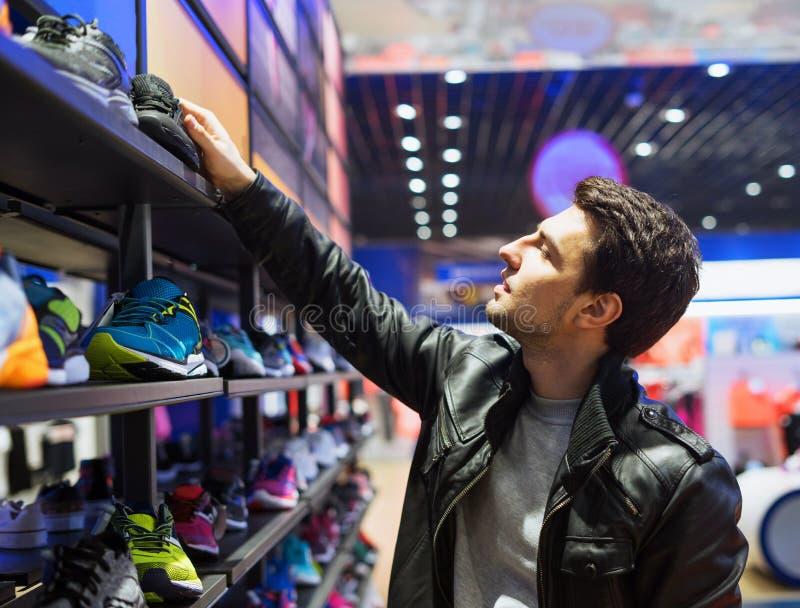 Cliente masculino novo que escolhe as sapatilhas na loja do supermercado fotografia de stock royalty free