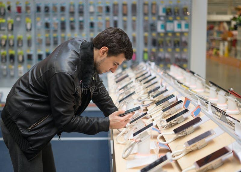 Cliente masculino novo que escolhe o smartphone imagens de stock royalty free